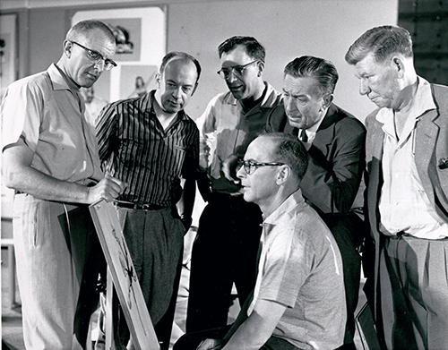 L-R Milt Kahl, Marc Davis, Frank Thomas,  Walt, and Wilfred Jackson watch Ollie Johnston at work, 1957; collection of Ollie Johnston, ©  Disney.